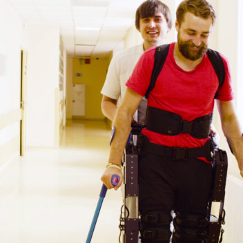 Young disable man in the robotic exoskeleton